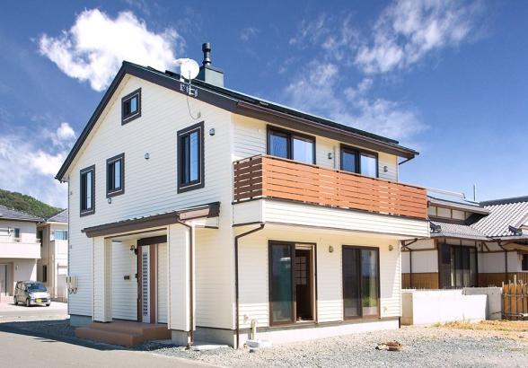 淡いカラーの外壁が青空にすっきりと映える邸宅